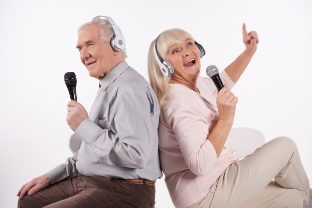 casal-de-idosos-em-fones-de-ouvido-esta-cantando-karaoke_99043-1615