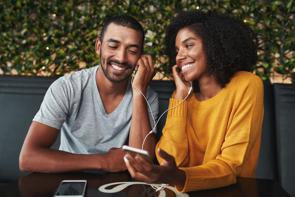 Portrait of an african young couple together listening music in cafe on one earphone