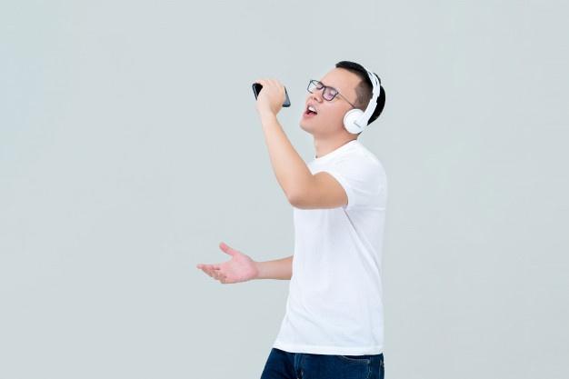 homem-asiatico-usando-fones-de-ouvido-ouvindo-musica-e-cantando_8087-3875